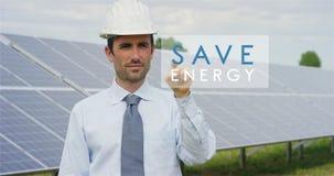 Un experto técnico futurista en los paneles fotovoltaicos solares, selecciona la función del ` de la energía de la reserva del `  Fotografía de archivo libre de regalías