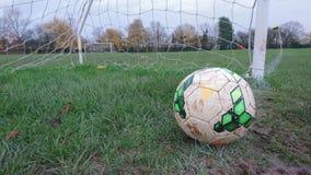 Un fútbol en la línea de meta de un campo de fútbol fangoso Imagenes de archivo
