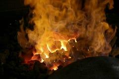 Un fabbro sul lavoro con i ferri d'ardore Forgia calda del ferro, il nero Immagini Stock Libere da Diritti