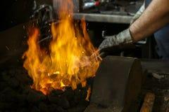 Un fabbro sul lavoro con i ferri d'ardore Forgia calda del ferro, il nero Fotografie Stock