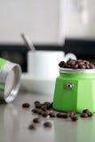 Un fabricant d'expresso italien vert de tasse avec des haricots d'expresso, tasse et soucoupe Photo libre de droits