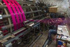 Un fabricant de tissu de slik maintient un oeil étroit sur sa machine à Varanasi Photographie stock
