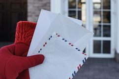 Un facteur de femme dans les gants rouges soutient plusieurs enveloppes de courrier au destinataire dans une maison privée Images libres de droits