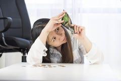 Un fallimento, si è rotto e la donna frustrata sta avendo problemi finanziari con le monete lasciate sulla tavola e su un portafo immagine stock