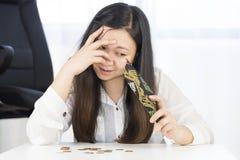 Un fallimento, si è rotto e la donna frustrata sta avendo problemi finanziari con le monete lasciate sulla tavola e su un portafo fotografie stock