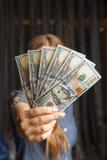Un fan di 100 banconote del dollaro in mani della donna Immagini Stock