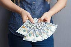 Un fan di 100 banconote del dollaro in mani della donna Fotografia Stock