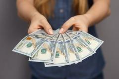 Un fan di 100 banconote del dollaro in mani della donna Fotografie Stock Libere da Diritti
