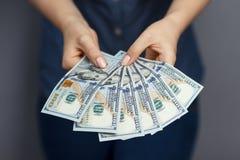 Un fan di 100 banconote del dollaro in mani della donna Immagine Stock