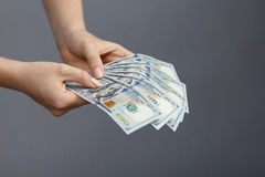 Un fan di 100 banconote del dollaro in mani della donna Fotografia Stock Libera da Diritti