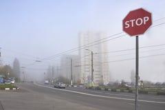 Un fanale di arresto che affronta la strada con nebbia immagini stock