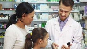 Un farmacéutico joven habla de uno de los productos de la farmacia a sus clientes almacen de metraje de vídeo