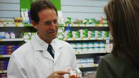 Un farmacéutico que aconseja a un cliente en la medicación almacen de video