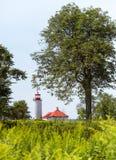 Un faro coperto rosso incorniciato dagli alberi fotografie stock