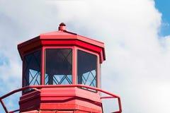 Un faro rojo aislado con las nubes imagen de archivo