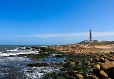 Un faro vicino ad una spiaggia Fotografia Stock Libera da Diritti