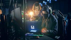Un femenino y los piratas informáticos de sexo masculino se está rompiendo en los servidores almacen de video