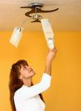 Un femme changeant l'ampoule photo stock