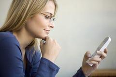 Un femme composant son téléphone Photographie stock
