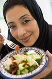 Un femme du Moyen-Orient avec une plaque de salade image libre de droits