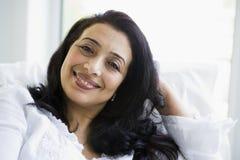Un femme du Moyen-Orient s'asseyant à la maison images stock