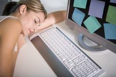 Un femme en sommeil à son ordinateur Image stock
