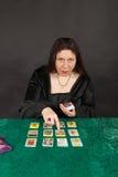 Un femme est des cartes de tarot du relevé Image stock