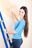 Un femme est des murs de peinture Photos stock