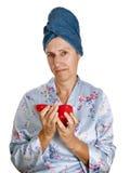 Un femme plus âgé avec le cheveu en essuie-main appliquant la crème de visage Photo libre de droits
