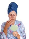 Un femme plus âgé avec le miroir dans la robe de chambre Photographie stock libre de droits