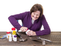Un femme plus âgé luttant pour ouvrir une bouteille de médecine Image stock