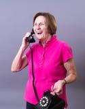 Un femme plus âgé riant au téléphone Photographie stock