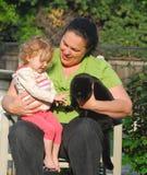 Un femme présente un enfant en bas âge à un chat noir Image libre de droits