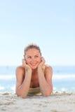 Un femme s'exposant au soleil à la plage Photo stock