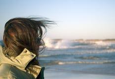 Un femme à une mer très venteuse Photo stock