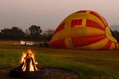 Un feu brûle pendant le début de la matinée avant un vol chaud de ballon à air Images stock