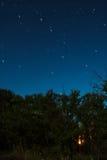 Un feu brûle à l'intérieur de la forêt dans une nuit de pleine lune avec des traînées d'une étoile de constellation d'Ursa Major Photo stock
