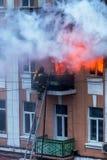 Un feu dans un immeuble Lumière et clubs lumineux forts, fenêtre de nuages de fumée de leur maison brûlante sapeurs-pompiers image stock