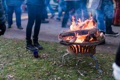 Un feu ouvert chauffe les visiteurs à la foire de Noël par le lac, K Photo libre de droits