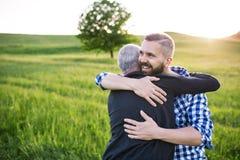 Un figlio adulto dei pantaloni a vita bassa con il padre senior su una passeggiata in natura al tramonto, abbracciante fotografia stock libera da diritti