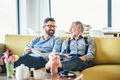 Un figlio adulto dei pantaloni a vita bassa e un padre senior che si siedono sul sofà all'interno a casa, parlando immagini stock