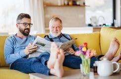 Un figlio adulto dei pantaloni a vita bassa e un padre senior che si siedono sul sof? all'interno a casa, parlando fotografie stock libere da diritti