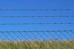 Un fil et une barrière barbelés en métal contre le ciel bleu 2 Photo stock