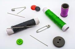 Un filato, aghi e bottoni Immagine Stock