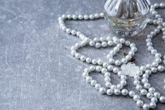 Un filo delle perle e del profumo su un fondo di pietra Immagine Stock