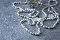 Un filo delle perle e del profumo su un fondo di pietra Fotografia Stock Libera da Diritti