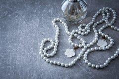 Un filo delle perle e del profumo su un fondo di pietra Fotografia Stock