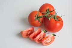 Un filo di tre interi pomodori della capriata e dei pomodori affettati Fotografia Stock