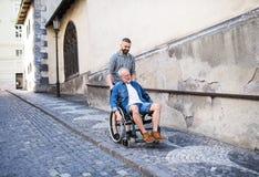 Un fils adulte avec le père supérieur dans le fauteuil roulant sur une promenade en ville photo libre de droits