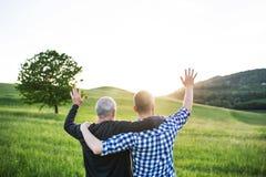 Un fils adulte de hippie avec le père supérieur sur une promenade en nature au coucher du soleil, bras autour de l'un l'autre Photographie stock